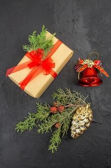 Bovenaanzicht kerstcadeau in bruin papier gebonden met rood lint dennentak kerstboomversieringen op donkere ondergrond