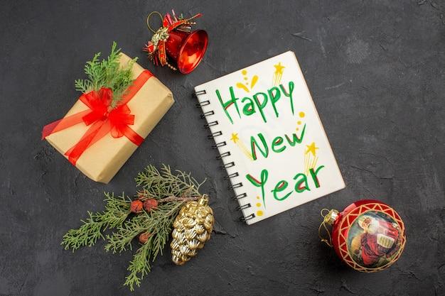 Bovenaanzicht kerstcadeau in bruin papier gebonden met rood lint en nieuwjaar geschreven op notitieboekje op donkere achtergrond