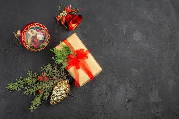 Bovenaanzicht kerstcadeau in bruin papier gebonden met rood lint kerstboom ornamenten op donkere achtergrond kopie ruimte