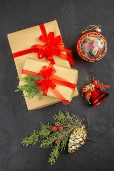 Bovenaanzicht kerstcadeau in bruin papier gebonden met rood lint kerstboomversieringen op donkere achtergrond