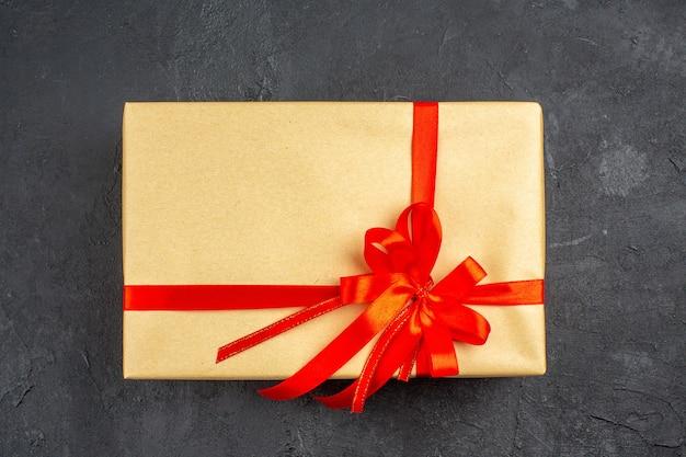 Bovenaanzicht kerstcadeau in bruin papier gebonden met rood lint op donkere ondergrond