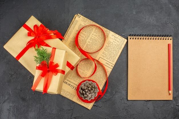 Bovenaanzicht kerstcadeau in bruin papier tak dennenlint op kranten dennenappel een notitieblok potlood op donkere ondergrond