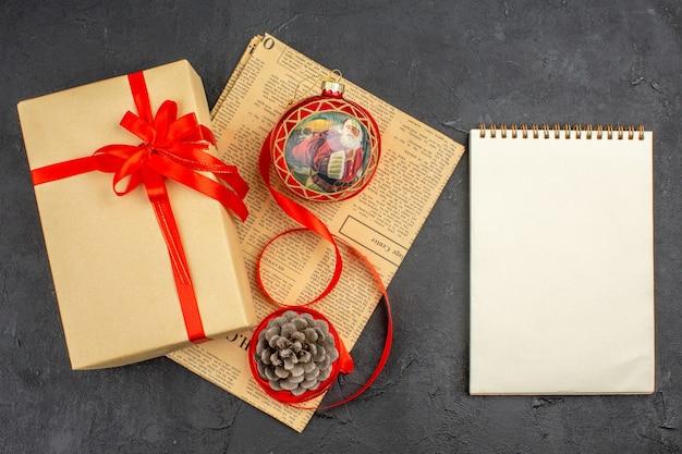 Bovenaanzicht kerstcadeau in bruin papieren lint kerstboom speelgoed op krant een notitieboekje op donkere ondergrond