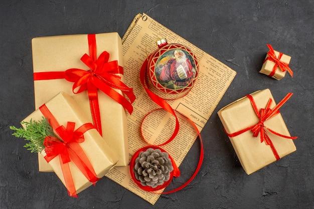 Bovenaanzicht kerstcadeau in bruin papieren lint kerstboom speelgoed op krant op donkere ondergrond