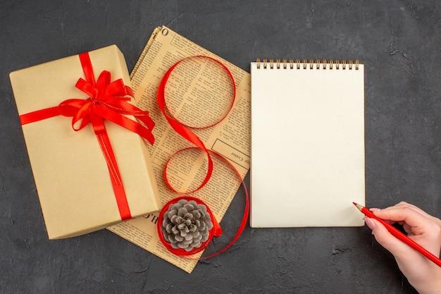 Bovenaanzicht kerstcadeau in bruin papieren lint op krant een notitieboekje rood potlood in vrouwelijke hand op donkere ondergrond