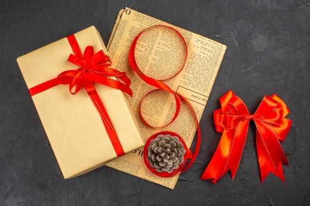 Bovenaanzicht kerstcadeau in bruin papieren lint op krant rode strik op donkere ondergrond