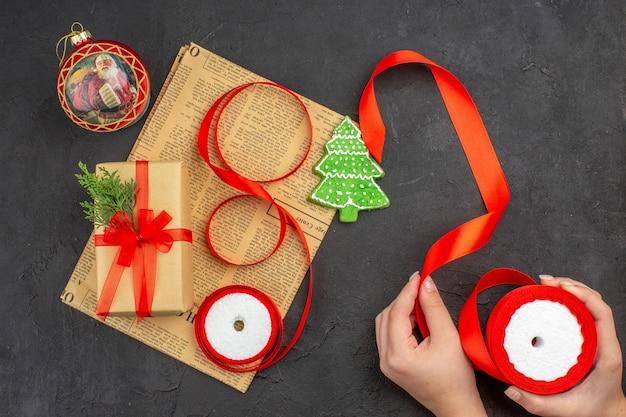Bovenaanzicht kerstcadeau in bruine papieren tak dennenlint op krantenlint in vrouwelijke hand op donkere ondergrond