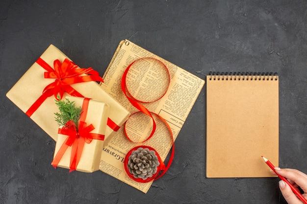 Bovenaanzicht kerstcadeau in bruine papieren tak spar lint op krant dennenappel notitieblok rood potlood in vrouwelijke hand op donkere ondergrond