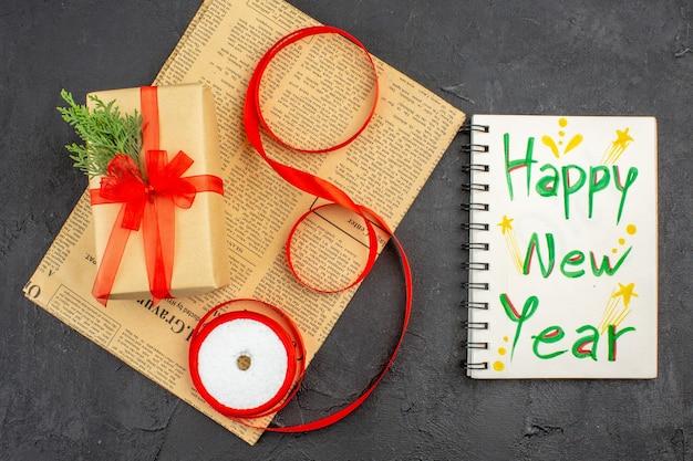 Bovenaanzicht kerstcadeau in bruine papieren tak spar lint op krant gelukkig nieuwjaar geschreven op notitieblok op donkere ondergrond
