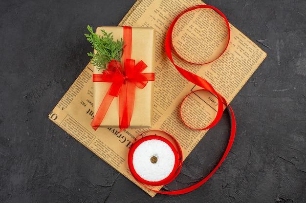 Bovenaanzicht kerstcadeau in bruine papieren tak spar lint op krant op donkere ondergrond
