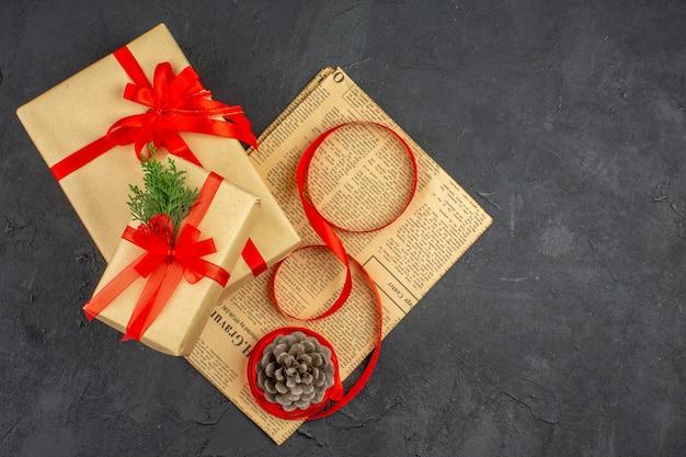 Bovenaanzicht kerstcadeau in bruine papieren tak spar lint op kranten dennenappel op donkere ondergrond