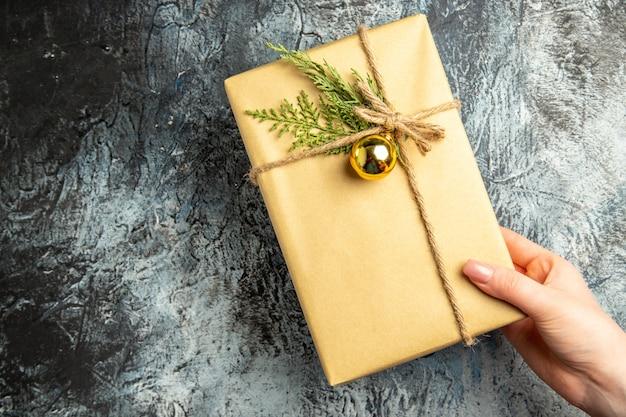 Bovenaanzicht kerstcadeau in vrouwelijke hand op grijs oppervlak