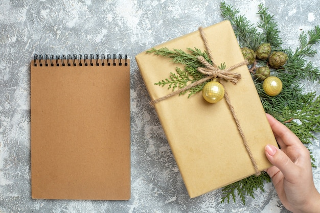 Bovenaanzicht kerstcadeau met groene tak en notitieblok op wit xmas kleur vakantie foto cadeau nieuwjaar