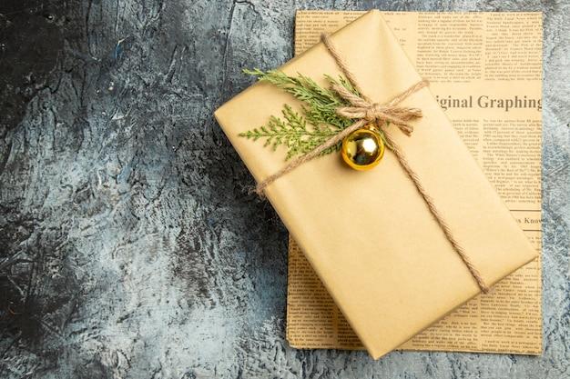 Bovenaanzicht kerstcadeau op krant op grijs oppervlak