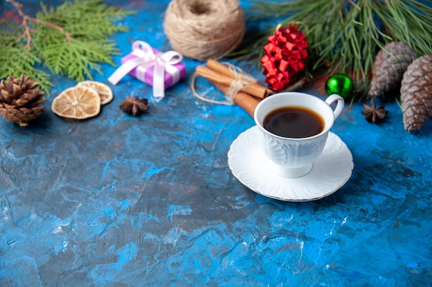 Bovenaanzicht kerstcadeaus dennenboom takken kegels anijs kopje thee op blauwe achtergrond vrije plaats