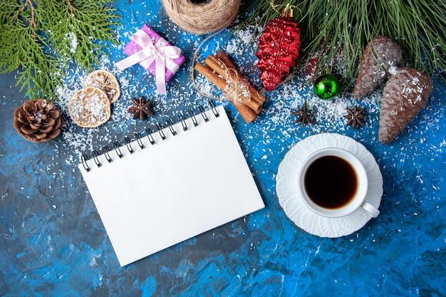Bovenaanzicht kerstcadeaus dennenboom takken kegels anijs notitieboekje een kopje thee op blauwe ondergrond