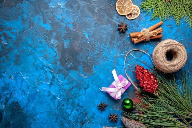 Bovenaanzicht kerstcadeaus dennenboom takken kegels anijs op blauwe ondergrond