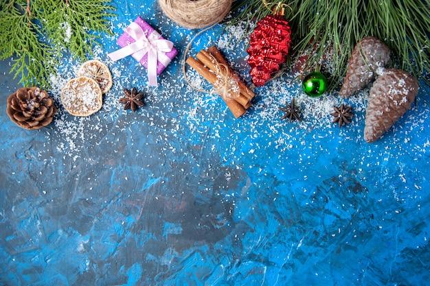 Bovenaanzicht kerstcadeaus fir tree takken kegels anijs op blauwe achtergrond