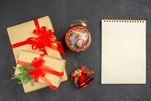 Bovenaanzicht kerstcadeaus in bruin papier gebonden met rood lint kerstboom speelgoed notitieblok op donkere ondergrond