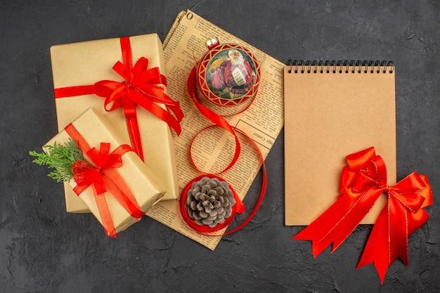 Bovenaanzicht kerstcadeaus in bruin papieren lint kerstboom speelgoed op krant rode strik op notebook op donkere ondergrond