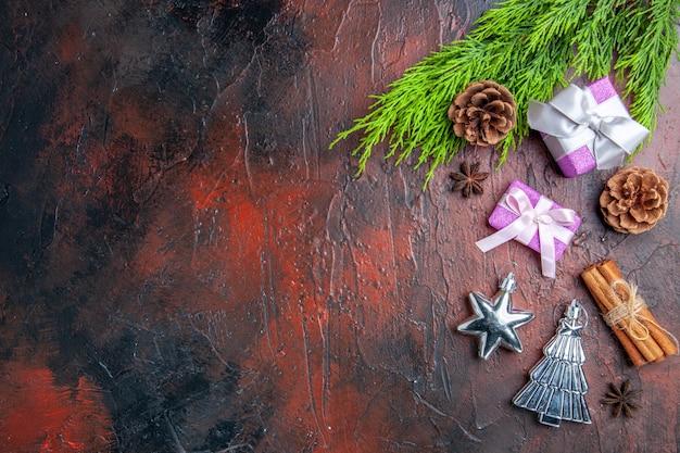 Bovenaanzicht kerstcadeaus met roze doos en wit lint boomtak anijs kaneel kerstboom speelgoed op donkerrood oppervlak