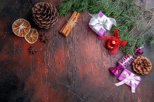 Bovenaanzicht kerstcadeaus pijnboomtakken met kegel kerstboomspeelgoed kaneel gedroogde citroenschijfjes anijs op donkerrood oppervlak