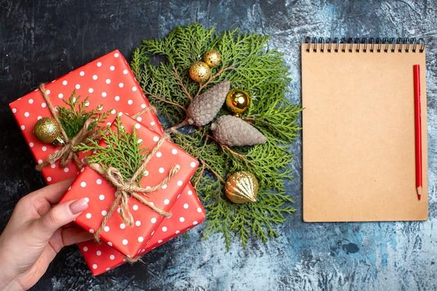 Bovenaanzicht kerstcadeautjes en leeg notitieboekje met rood potlood