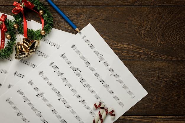 Bovenaanzicht kerstmuziek notitiepapier met kerstkrans op houten achtergrond en kopieer ruimte.