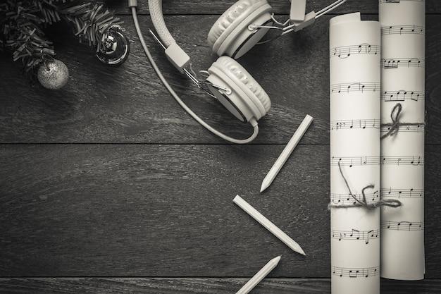 Bovenaanzicht kerstmuziek notitiepapier met kerstversiering en koptelefoon op houten tafelachtergrond. maak zelf dit muzieknota papier.