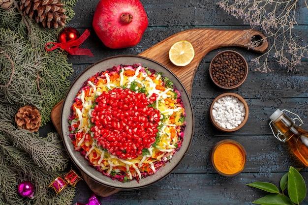 Bovenaanzicht kerstschotel kerstschotel op het bord naast de granaatappel kleurrijke kruiden olie en takken met kegels kerstboomspeelgoed