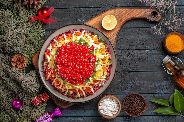 Bovenaanzicht kerstschotel met granaatappel op het bord naast de kruidenfles olie en sparren takken met kerstboomspeelgoed