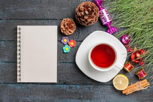 Bovenaanzicht kerstspeelgoed vuren takken met kerstspeelgoed en kegels naast het kopje thee op de witte schotel witte notebook kaneelstokjes en citroen op tafel