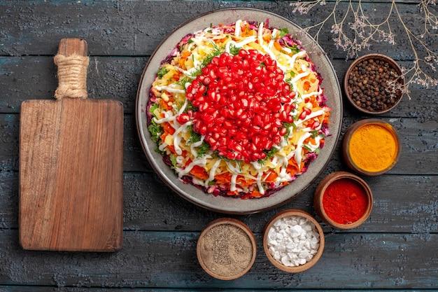 Bovenaanzicht kerstvoedsel kerstschotel met aardappelen, wortelen, bieten, granaatappel en mayonaise naast de kommen met kleurrijke kruiden, snijplank en boomtakken