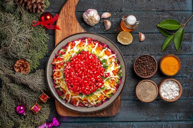 Bovenaanzicht kerstvoedsel op het bord bord met kerstgerecht aan boord naast de takken met kegels olie kommen kruiden knoflook citroen