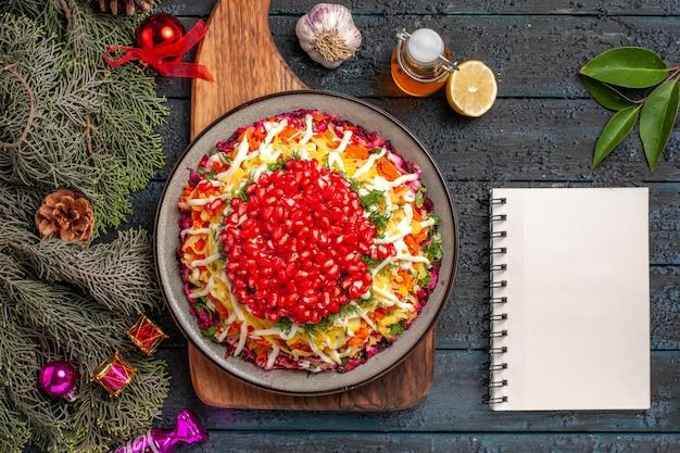 Bovenaanzicht kerstvoedsel op het bord met kerstschotel aan boord naast de witte notebookfles olietakken met kegels kom kruiden knoflook citroen