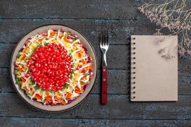 Bovenaanzicht kerstvoedsel smakelijke kerstschotel met zaden van granaatappel naast de vorkboomtakken en wit notitieboekje op de grijze tafel