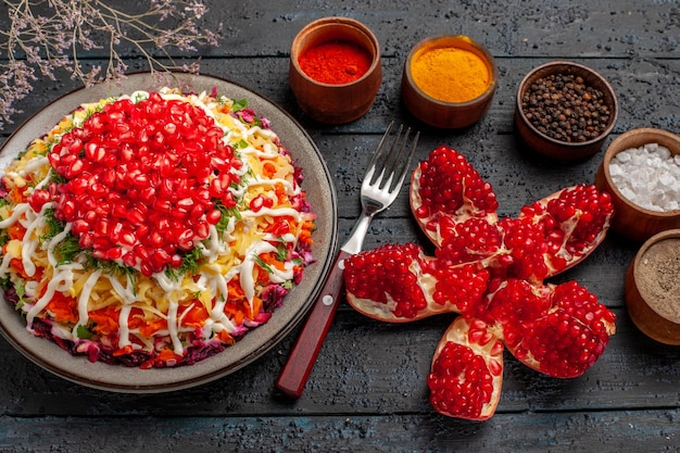 Bovenaanzicht kerstvoedsel vijf kommen met kleurrijke kruiden naast de gepelde granaatappelvork kerstschotel met zaden van granaatappel en boomtakken