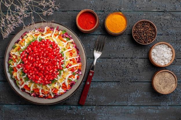 Bovenaanzicht kerstvoedsel vijf kommen met kleurrijke kruiden naast de vork kerstschotel met zaden van granaatappel en boomtakken