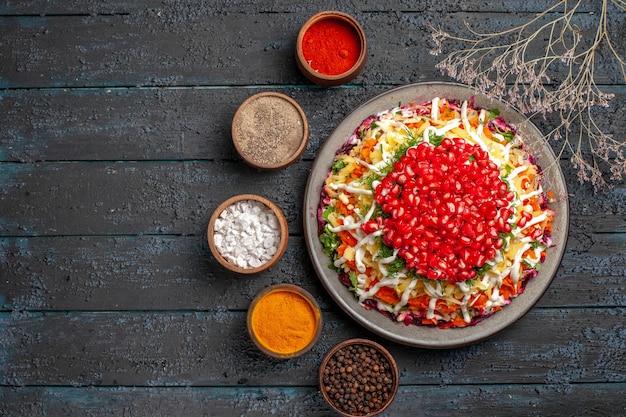 Bovenaanzicht kerstvoedsel witte plaat van kerstschotel met zaden van granaatappel naast de boomtakken en kommen met kleurrijke kruiden op tafel
