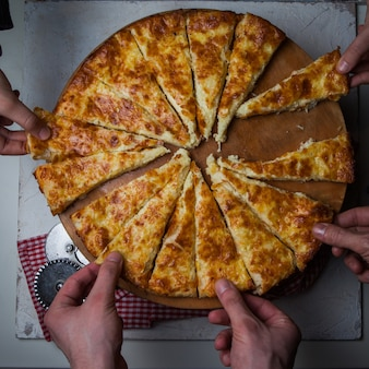 Bovenaanzicht khachapuri met pizza snijmes en menselijke handen en servetten