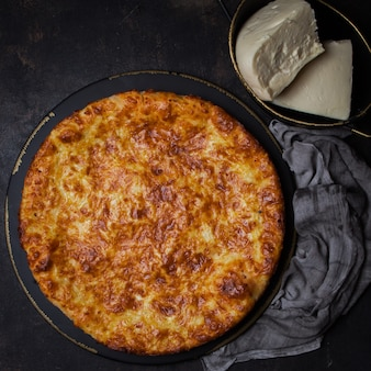 Bovenaanzicht khachapuri met sulguni kaas in donkere plaat