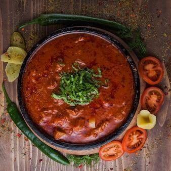 Bovenaanzicht kharcho met groene paprika en tomaat en groenen in donkere plaat