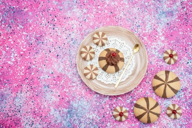 Bovenaanzicht kies koekjes heerlijk en lekker op het gekleurde bureau koekje chocolade zoete kleur