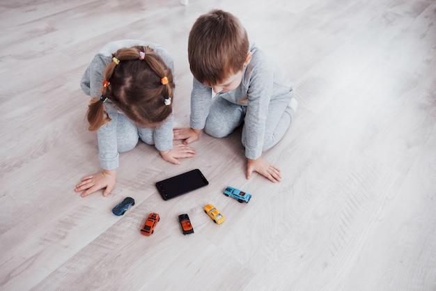 Bovenaanzicht. kinderen gebruiken digitale gadgets thuis. broer en zus op pyjama kijken naar tekenfilms en spelen spelletjes op hun technologietablet