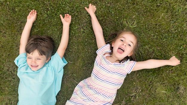Bovenaanzicht kinderen gelegd op gras