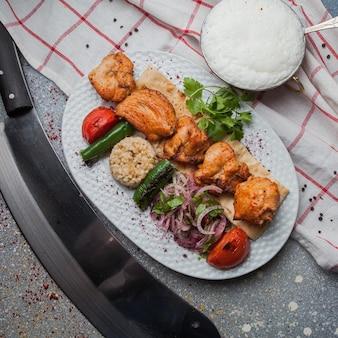 Bovenaanzicht kip kebab met gebakken groenten en gehakte ui en ayran en mes in witte plaat