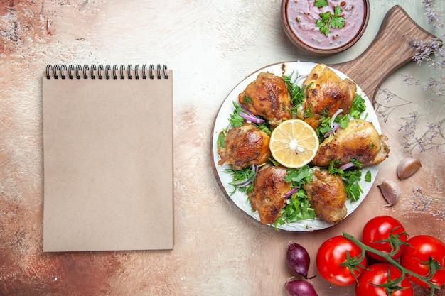 Bovenaanzicht kip kip met kruiden citroen op het bord tomaten saus room notebook
