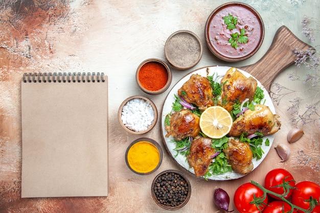 Bovenaanzicht kip kip met kruiden citroen tomaten saus kruiden room notebook
