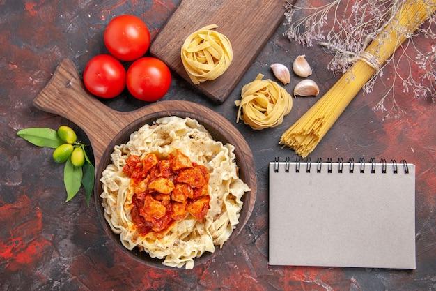 Bovenaanzicht kip met deeg pasta schotel met tomaten donkere oppervlak pasta deeg maaltijd
