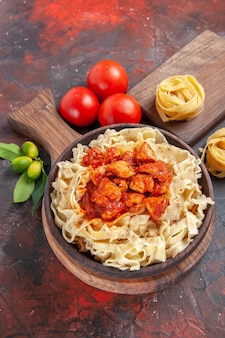 Bovenaanzicht kip met deeg pasta schotel met tomaten op donkere bureau deegwaren maaltijd